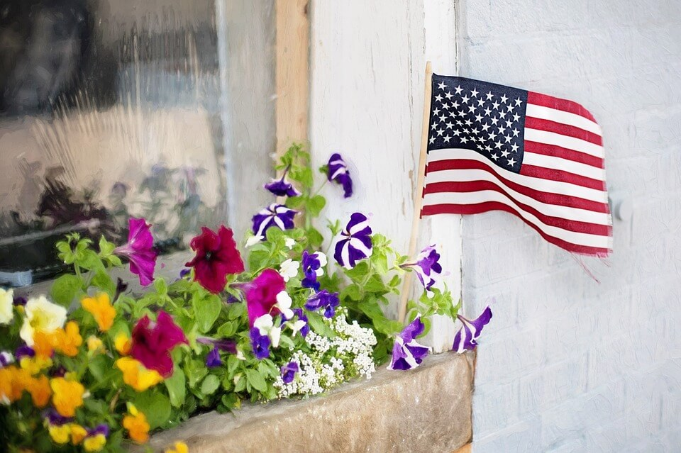 Small US Flag waving beside colorful flowers
